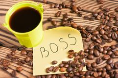 Full green metal bucket of black coffee near paper sticker with inscription boss and scattered lot of roasted beans. On old worn wooden table royalty free stock photos