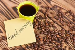 Full green metal bucket of black coffee near paper sticker with inscription good morning and scattered lot of roasted beans. On old worn wooden table royalty free stock image