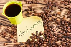 Full green metal bucket of black coffee near paper sticker with inscription good morning and scattered lot of roasted beans. On old worn wooden table stock photos