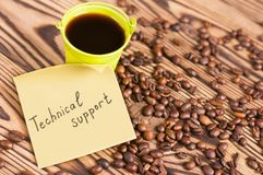 Full green metal bucket of black coffee near paper sticker with inscription technical support and scattered lot of roasted beans. On old worn wooden table royalty free stock photo