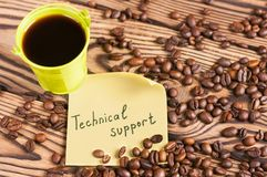 Full green metal bucket of black coffee near paper sticker with inscription technical support and scattered lot of roasted beans. On old worn wooden table royalty free stock images