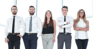 In full growth.modern business team standing in a bright office. The concept of professionalism stock image