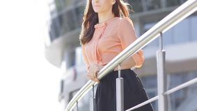 In full growth.modern woman against the background of an office building stock images