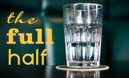 The Full Half Concept. A half full glass of water symbolizing optimism versus pessimism Stock Image