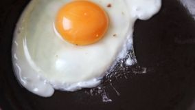 A broken egg on a pan. Full HD video of broken egg, frying in a black pan stock video footage