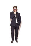 Full height Cheerful young handsome man in sunglasses keeping hand on chin Royalty Free Stock Image
