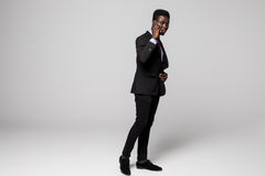 Full height Confident young African man talking on mobile phone while standing against grey background Stock Photo