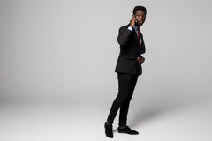 Full height Confident young African man talking on mobile phone while standing against grey background Stock Photos