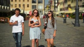 Full Height Portrait of Two Beautiful Girls and One Handsome Boy with Beverages in the Hands.Three Happy Smiling Friends. Drinking Coffee while Walking around stock video
