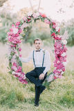The full-hight portrait of the best man sitting on the peonies arch located in the sunny park. Stock Images