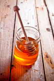 Full honey pot and honey stick Stock Photos