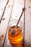 Full honey pot and honey stick Royalty Free Stock Photography