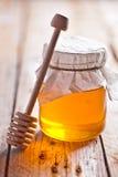 Full honey pot and honey stick Stock Photography