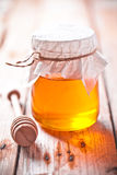 Full honey pot and honey stick Royalty Free Stock Image