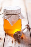 Full honey pot and honey stick Stock Photography