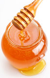 Full honey pot and spilled honey. On a white background stock image