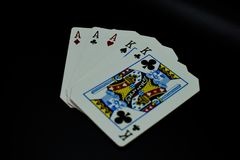 Full house aces full of kings of cards in poker game against black background royalty free stock photos