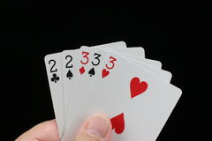 Full House poker hand. Poker hand with full house with twos and threes on a black background stock photo