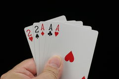 Full house poker hand. Poker hand with a full house of aces and twos on a black background Stock Photos