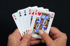 Full house poker hand. Woman holding playing cards of a full house poker hand against a black background royalty free stock photos