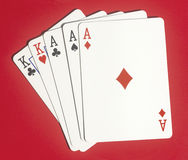Full House Poker Playing Cards. Full house Poker hand on red background, drop shadow, showing whole playing cards. Copyspace Stock Photo