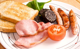 Full Irish Breakfast. Selective focus of an Irish breakfast with Black pudding, Rashers, Sausages, tomato and toast Royalty Free Stock Photos