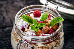 Full jar of muesli, yogurt, raspberries, nuts on a black, burnt wood table. Homemade breakfast cereals food. Healthy eating Royalty Free Stock Photos