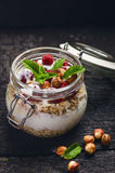 Full jar of muesli, yogurt, raspberries, nuts on a black, burnt wood table. Homemade breakfast cereals food. Healthy eating Stock Images