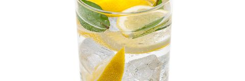 A full jug of drink from ice, lobules of fresh juicy yellow lemon and crystal clear water. A full jug of drink from ice, lobules of fresh yellow lemon and royalty free stock images
