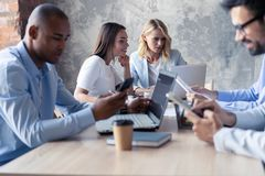 Full koncentration på arbete Grupp av ungt affärsfolk som arbetar och meddelar, medan sitta på kontorsskrivbordet royaltyfri bild