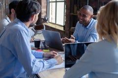 Full koncentration på arbete Grupp av ungt affärsfolk som arbetar och meddelar, medan sitta på kontorsskrivbordet arkivfoton