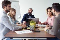 Full koncentration på arbete Grupp av ungt affärsfolk som arbetar och meddelar, medan sitta på kontorsskrivbordet arkivbild