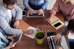Full koncentration på arbete Grupp av ungt affärsfolk som arbetar och meddelar, medan sitta på kontorsskrivbordet royaltyfria foton