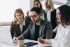 Full koncentration på arbete Grupp av ungt affärsfolk som arbetar och meddelar, medan sitta på kontorsskrivbordet tillsammans arkivbild