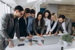 Full koncentration på arbete Grupp av ungt affärsfolk som arbetar och meddelar, medan stå i modernt kontor royaltyfri foto