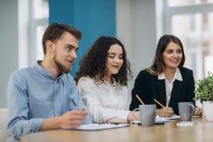 Full koncentration p? arbete Funktionsdugliga kollegor f?r f?retags lag som arbetar i modernt kontor arkivbild