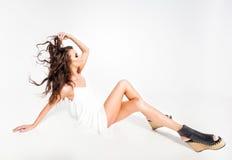 Full kropp av den härliga kvinnamodellen som poserar i den vita klänningen i studion royaltyfri foto