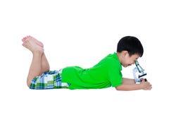 Full kropp av det asiatiska barnet som observeras till och med en mikroskopbiologica Arkivbild