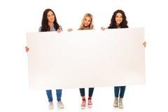 Full kroppbild av tre tillfälliga kvinnor som rymmer den stora affischtavlan Royaltyfria Bilder