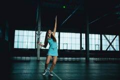Full kroppstående av ung flickatennisspelaren i handling i en tennisbana inomhus royaltyfri bild