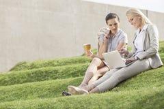 Full längd av affärskvinnor med den disponibla kaffekoppen som ser bärbara datorn, medan sitta på gräsmoment Arkivfoto