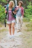 Full längd av att fotvandra par i skog Arkivfoto