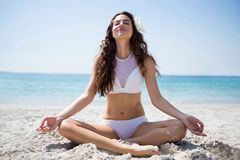 Full längd av att le kvinnan som mediterar, medan sitta på sand Arkivbilder