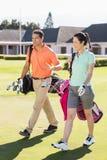 Full längd av bärande golfpåsar för par Royaltyfri Fotografi
