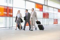 Full längd av businesspeople med bagage som går på järnvägplattformen Royaltyfri Bild