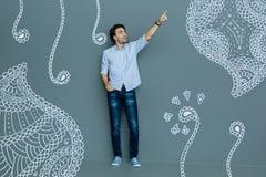 Full längd av den förtjusta stiliga mannen som pekar upp med hans pekfinger Royaltyfri Fotografi