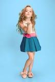 Full längd av den härliga lilla flickan i klänningen som står och poserar över blå bakgrund royaltyfria foton