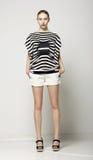 Full längd av den moderiktiga kvinnan i kortslutningar och Grey Striped Shirt. Tillfällig modern samling Fotografering för Bildbyråer