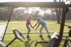 Full längd av den mogna manundervisningkvinnan som spelar golf Arkivbild