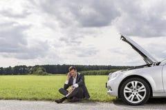 Full längd av den olyckliga unga affärsmannen som ner använder mobiltelefonen med den brutna bilen på bygd Royaltyfria Bilder